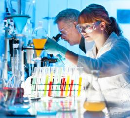 medical red-haired-woman-and-gray-haired-man-in-chemistry-lab-with-beakers-and-test-tubes